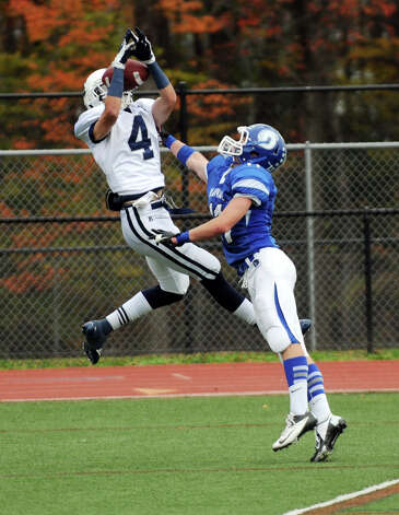 Darien's Brian Weigand, right, and Staples' James Frusciante battle for the ball as Darien High School hosts Staples in a football game in Darien, Conn., Oct. 27, 2012. Photo: Keelin Daly