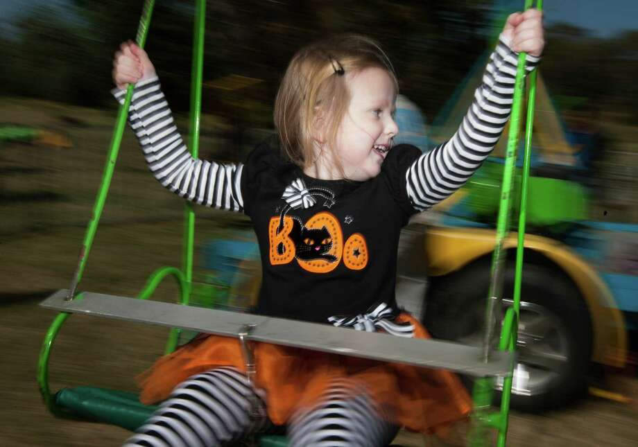 Sarah Park, 3, has some fun on the chair swings at the fourth annual Howl-O-Ween Fest 2012 at Bridgeland's Oak Meadow Park in Cypress on Saturday, Oct. 27, 2012, in Houston. Photo: J. Patric Schneider, For The Chronicle / © 2012 Houston Chronicle
