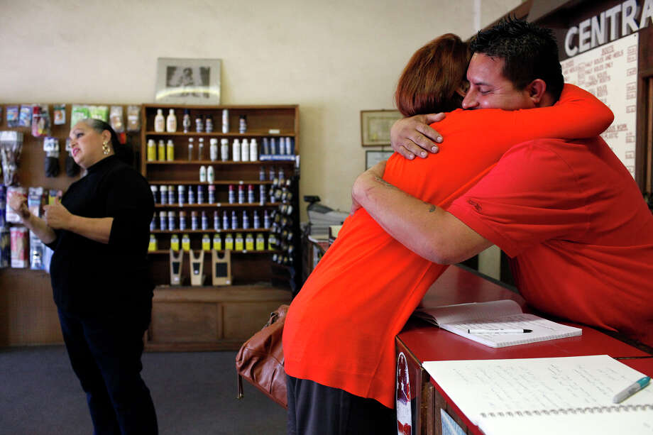 "Longtime customer Diane Rath embraces Bryan Rodriguez while his mother, Stela Salazar, chats with another client Saturday, the last day of the shop's operation for a while. ""It's just like family,"" Rath says of the Salazars. Photo: Lisa Krantz, San Antonio Express-News / San Antonio Express-News"