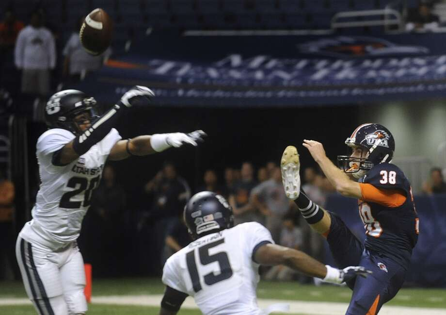 Devonta Glover-Wright (20) of Utah State blocks a punt by UTSA's Kristian Stern (38) as Jumanne Robertson of Utah State (15) approaches during WAC football action at the Alamodome on Saturday, Oct. 27, 2012. (Billy Calzada / San Antonio Express-News)