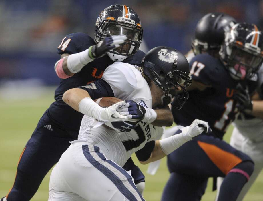 UTSA defender Triston Wade (14) wraps up Utah State receiver Travis Van Leeuwen in WAC football action at the Alamodome on Saturday, Oct. 27, 2012. (Billy Calzada / San Antonio Express-News)