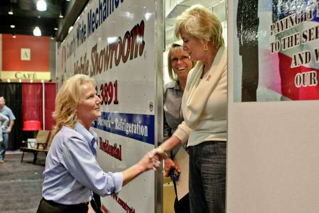 Republican U.S. Senate candidate Linda McMahon steps from the Country Wide Mechanical Services show-tralier at  the Fall Home Show at the Connecticut Convention Center on Saturday, Oct. 20, 2012.  McMahon greets Noralee Burby of Bristol as Cheryl Byrne of Burlington, center, smiles from within the tralier. Photo: Johnathon Henninger