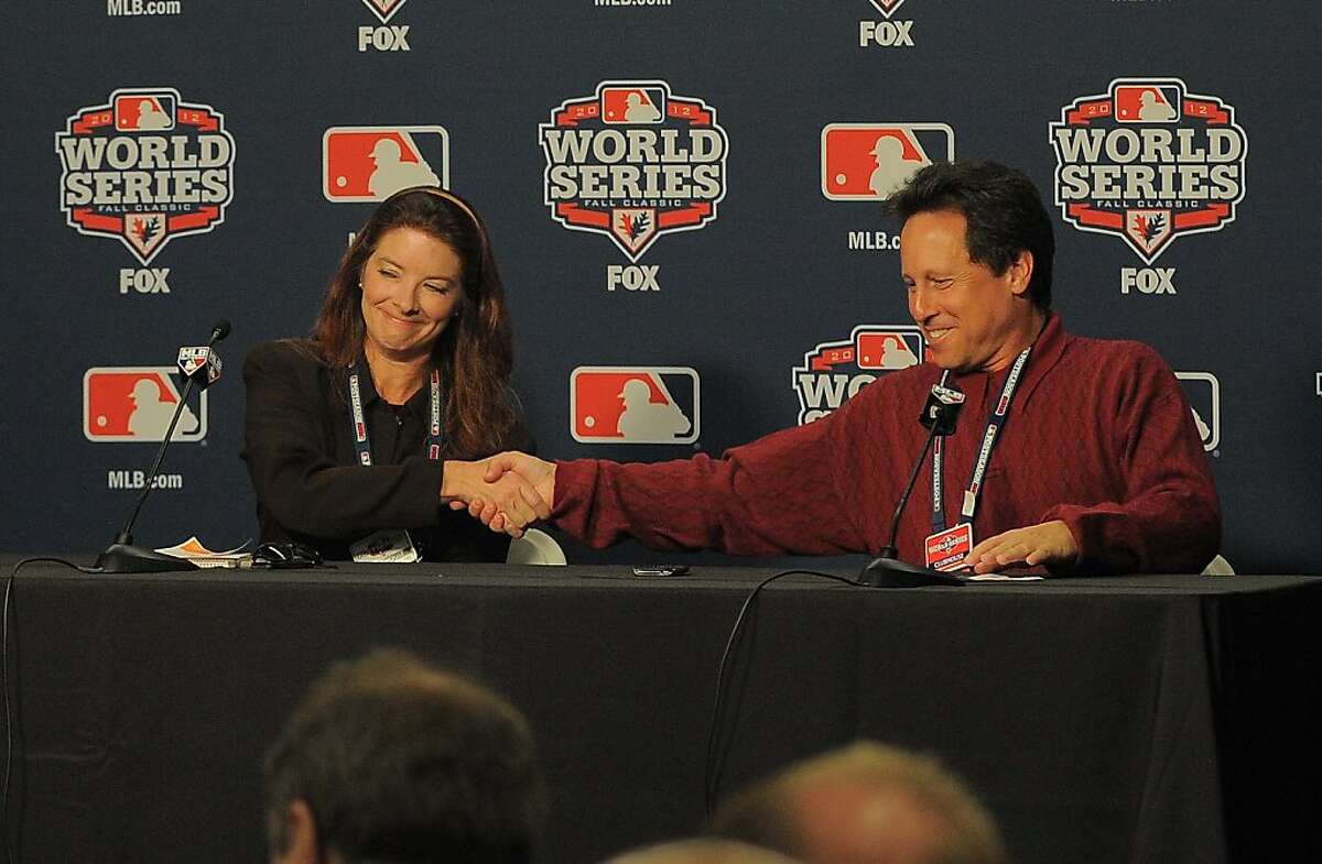 San Francisco sports columnist Susan Slusser and incoming president of the Baseball Writers Association of America shakes hands with LA Times sports writer Billy Shaikin, Saturday, October 27, 2012. Slusser is the first female president of the BBWAA.