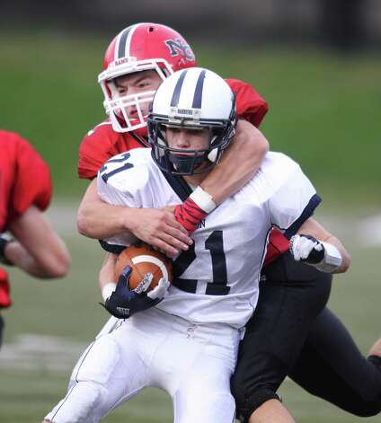 Wilton RB Nick Musicco is collared for a tackle by New Canaan defender Zach Laurinaitis during fourth quarter action in New Canaan. Led by QB junior quarterback Teddy Bossidy, the Rams won the tightly fought game, 21-14. Photo: J. Gregory Raymond