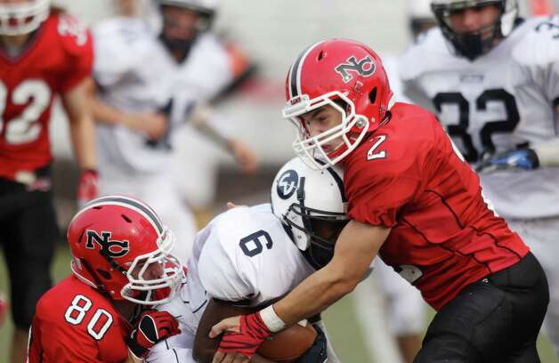 Wilton kick returner Rod-Djoly Thorby finds his path blocked by New Canaan tacklers Sterling Guynn and Cole Harriss in Saturday gridiron action.  New Canaan won the tightly fought game, 21-14. Photo: J. Gregory Raymond