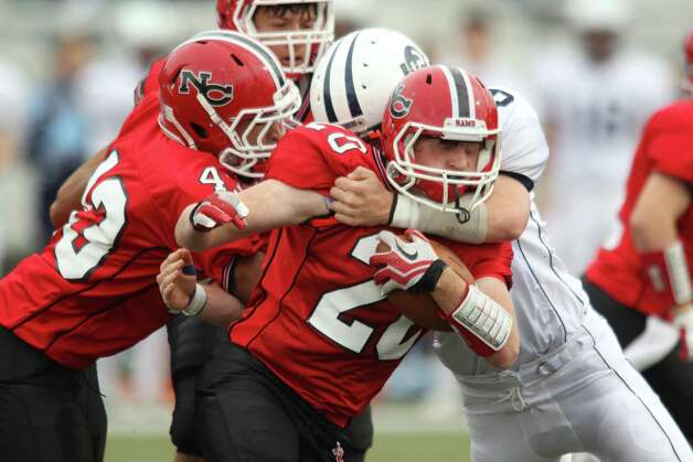 New Canaan wr Andrew Read is tackled for a short gain by Wilton Warrior Griffin Bender during FCIAC football action in New Canaan on Saturday. New Canaan won the tight battle, 21-14. Photo: J. Gregory Raymond