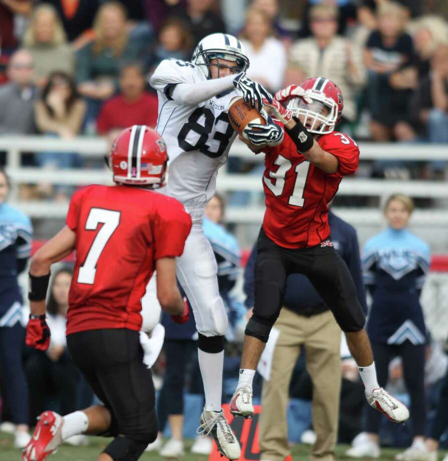 Wilton wide receiver Weston Wilbur attempts to snag a pass as New Canaan defender Mike DiCosmo defends. New Canaan won the tightly fought game 21-14. Photo: J. Gregory Raymond