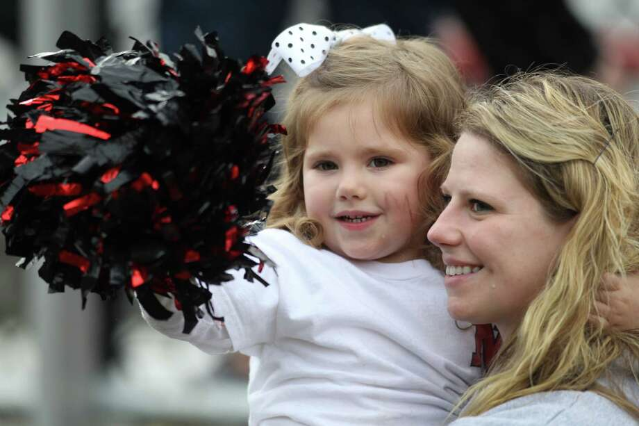 New Canaan pride was evident all over campus as the Ram's won a 21-14 homecoming game over Wilton. Here, a young fan and her friend cheer the Rams on. Photo: J. Gregory Raymond