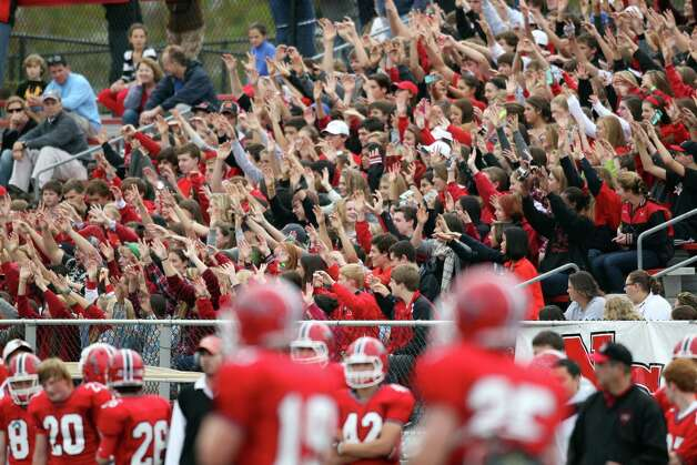 Showing its school pride, fans in the New Canaan stands cheer on its Ram team during a homecoming game against rival Wilton. New Canaan won the game, 21-14. Photo: J. Gregory Raymond