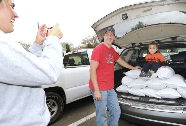 At left, Romina Puckett takes a photo of her husband, Jeff, and son, Holden, 14 months, with a vehicle-load of sandbags at the Sound Beach Firehouse in Old Greenwich, Saturday afternoon, Oct. 27, 2012. The Town of Greenwich provided the sandbags to residents with the hope that they wll help to prevent flooding from the approaching Hurricane Sandy. The Pucketts said they will be using the sandbags to try and prevent flooding at their home which is close to the water in Old Greenwich. Photo: Bob Luckey / Greenwich Time