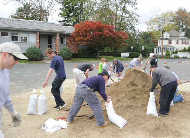 Greenwich residents fill sandbags at the Sound Beach Firehouse in Old Greenwich, Saturday afternoon, Oct. 27, 2012. The Town of Greenwich provided the sandbags to residents with the hope that they wll help to prevent flooding from the approaching Hurricane Sandy. Photo: Bob Luckey / Greenwich Time