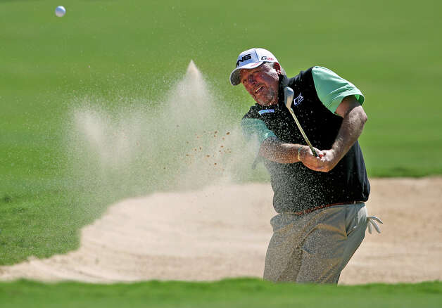 Mark Calcavecchia hits out of the sand to within a inches of the 12th pin for birdie during the second round of the 2012 AT&T Championship at the AT&T Canyons course on October 27, 2012. Photo: Tom Reel, Express-News / ©2012 San Antono Express-News