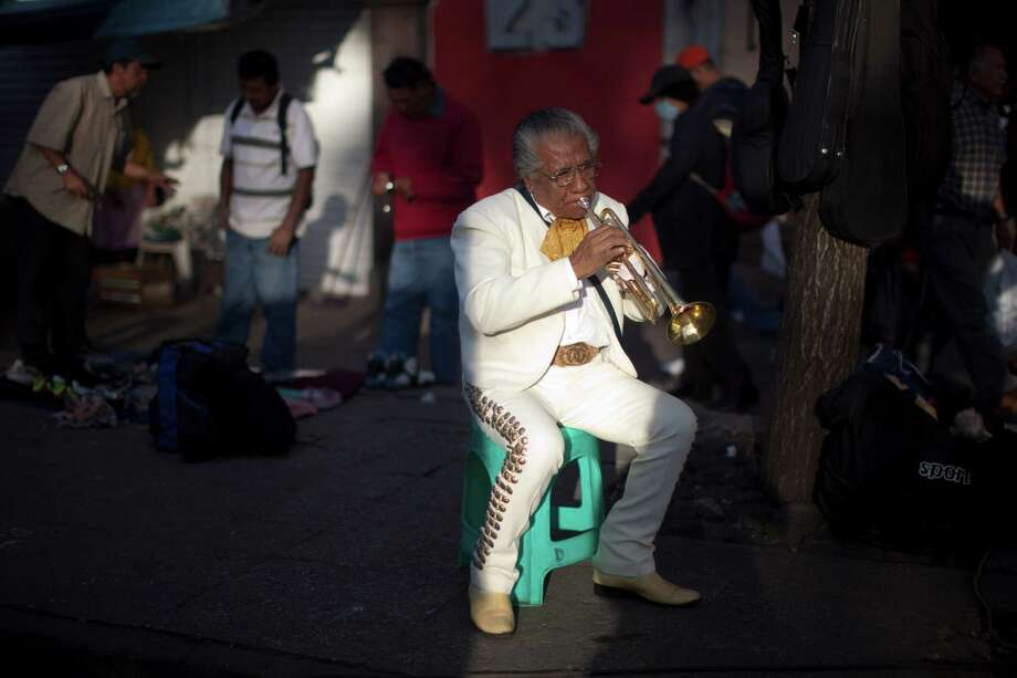 In this Oct. 5, 2012 photo photo, mariachi musician Jesus Velazquez practices his trumpet as he waits for clients at Plaza Garibaldi in Mexico City. The new Mariachi School Ollin Yoliztli in Mexico City is seeking to revive a music that's lost ground over the years. The school, whose name means life and movement in indigenous Nahautl, teaches folk bands how to play professionally while grooming a new generation of songwriters and composers. Photo: Alexandre Meneghini, Associated Press / AP