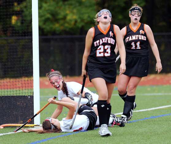 Elizabeth Stillman, lower left, of Greenwich, reacts with a shout to the goal scored by teammate Sydney Cole, on the ground, as Stamford's Ciara Killian # 23 and Erika Mikoshi # 11 walk away from the goal during the GreenwichFCIAC field hockey tournament match between Stamford High School and Greenwich High School at Greenwich, Saturday afternoon, Oct. 27, 2012. Photo: Bob Luckey / Greenwich Time