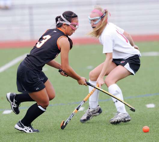 At left, Jasmine Li # 3 of Stamford gets past a Greenwich defender during the FCIAC field hockey tournament match between Stamford High School and Greenwich High School at Greenwich, Saturday afternoon, Oct. 27, 2012. Photo: Bob Luckey / Greenwich Time