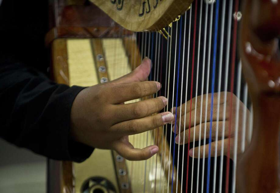 A Mexican musician Marco Antonio Berisntain plays his harp berfore an entrance examination at Ollin Yolitzli mariachi music school at the Garibaldi square in Mexico City on September 25, 2012. The school to mariachi musicians, the first one in Mexico City, will be opened next October. Mariachi was declared, last year, by UNESCO as Intangible Cultural Heritage of Humanity. Photo: Ronaldo Schemidt, AFP/Getty Images / AFP