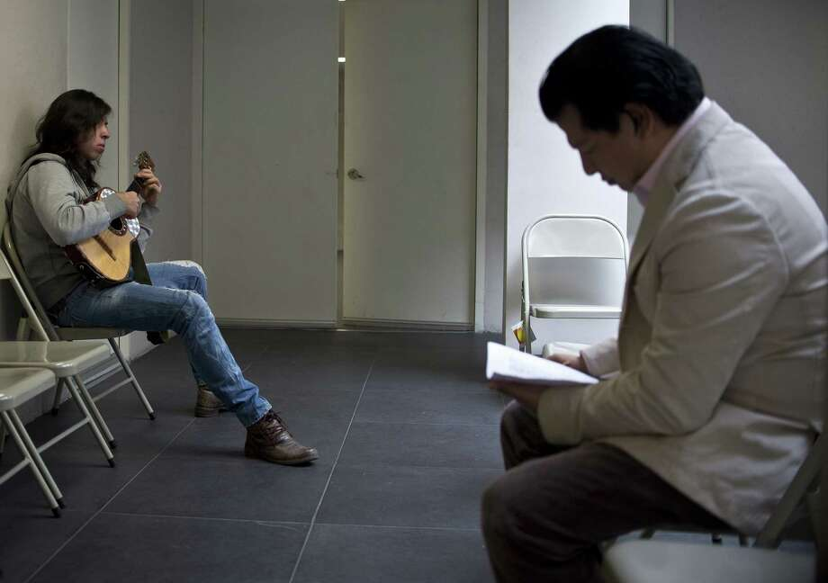 Mexican musician Gerardo Fuentes (L) plays his vihuela nexto to a teacher before an entrance examination at Ollin Yolitzli mariachi music school at the Garibaldi square in Mexico City on September 25, 2012. The school to mariachi musicians, the first one in Mexico City, will be opened next October. Mariachi was declared, last year, by UNESCO as Intangible Cultural Heritage of Humanity. Photo: Ronaldo Schemidt, AFP/Getty Images / AFP