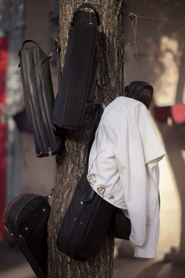 In this Oct. 5, 2012 photo photo, a mariachi musician's coat and instrument cases hang on a tree near Plaza Garibaldi in Mexico City. The new Mariachi School Ollin Yoliztli in Mexico City is seeking to revive a music that's lost ground over the years. The school, whose name means life and movement in indigenous Nahautl, teaches folk bands how to play professionally while grooming a new generation of songwriters and composers. Photo: Alexandre Meneghini, Associated Press / AP