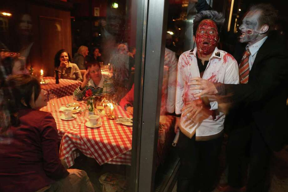 "Diners in a restaurant look on as zombie enthusiasts walk by during a ""Zombie Walk"" in the city center on October 27, 2012 in Berlin, Germany. Photo: Sean Gallup, Getty Images / 2012 Getty Images"