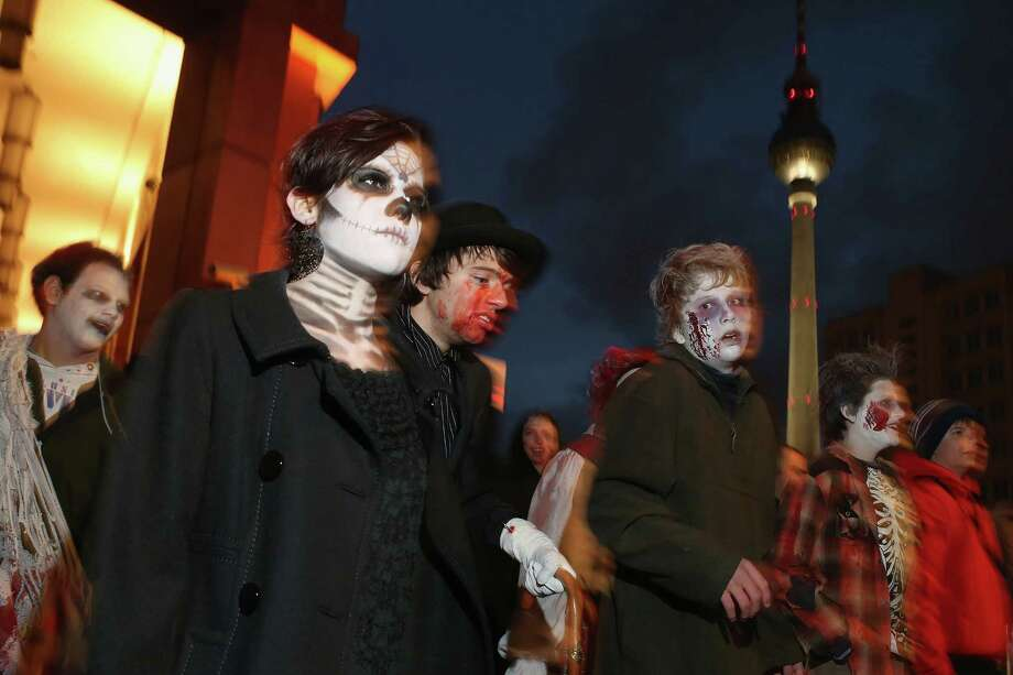 "Zombie enthusiasts  walk past the broadcast tower at Alexanderplatz during a ""Zombie Walk"" in the city center on October 27, 2012 in Berlin, Germany. Photo: Sean Gallup, Getty Images / 2012 Getty Images"