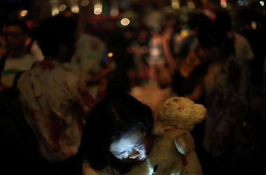 People dressed as ghouls and zombies gather at a popular night spot in Singapore on Saturday Oct. 27, 2012 as part of Halloween celebrations. (AP Photo/Wong Maye-E) Photo: Wong Maye-E, Associated Press / AP