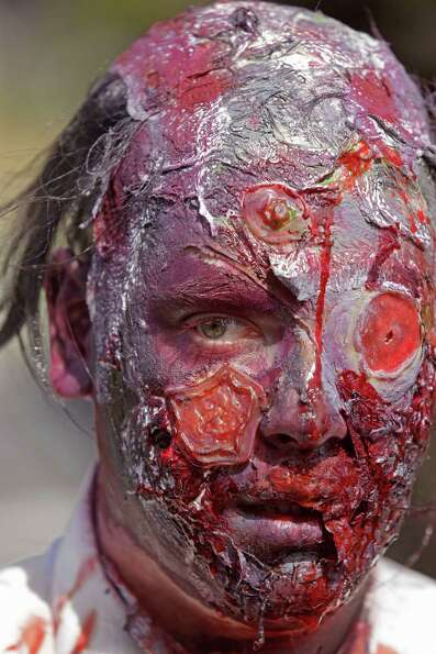 A man with his face covered in fake blood as he and others take part in Zombie Walk in  Cape Town, S