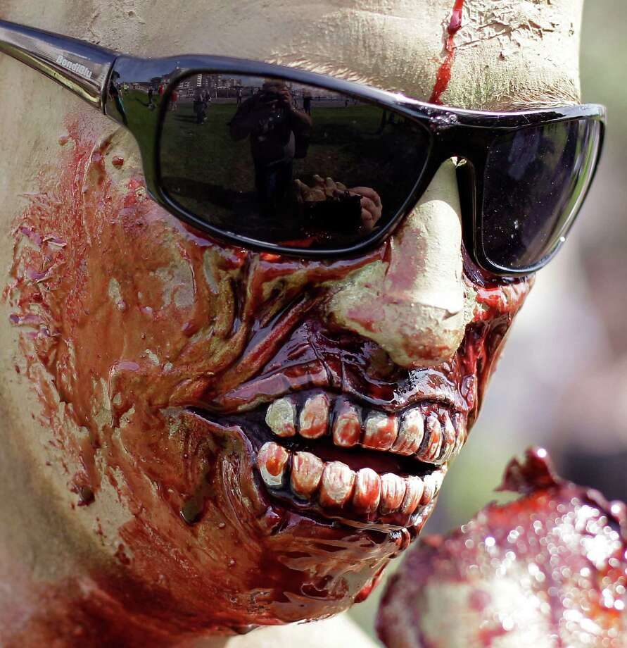 A man covered in what looks like blood is wearing a mask as he and others take part in Zombie Walk in Cape Town, South Africa, Saturday, Oct 27, 2012. Hundreds of people took part in a Zombie walk as part of yearly Halloween celebrations across the world with 31 Oct. being Halloween day. (AP Photo/Schalk van Zuydam) Photo: Schalk Van Zuydam, Associated Press / AP