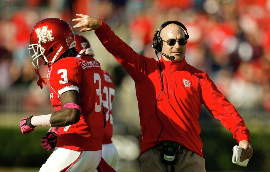 Houston head coach Tony Levine slaps Houston defensive back Earl Foster's (30) helmet after Foster scored a touchdown during the first quarter of a NCAA football game, Saturday, Oct. 27, 2012, in Robertson Stadium in Houston.  ( Nick de la Torre / Houston Chronicle ) \ Photo: Nick De La Torre, Houston Chronicle / Houston Chronicle