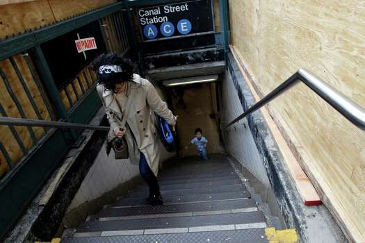 Commuters exit an entrance to the Canal St. A C and E station boarded up with plywood to help prevent flooding, Saturday, Oct. 27, 2012 in New York. As Hurricane Sandy approaches the New York region, residents of some flood-prone areas have been told to evacuate and officials are preparing for a possible transit system shutdown. (AP Photo/Mary Altaffer) Photo: Mary Altaffer