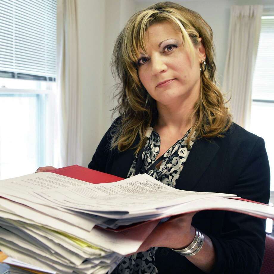 Jennifer Burkey holds a stack of papers pertaining to her order of protection in a domestic abuse case, revealing how law enforcement repeatedly failed to properly enforce laws and protect her, at her Hudson Falls office Tuesday, Oct. 23, 2012. (John Carl D'Annibale / Times Union) Photo: John Carl D'Annibale / 10019782A