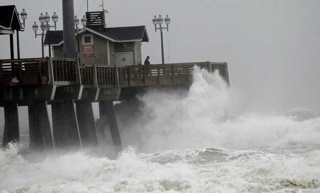 Large waves generated by Hurricane Sandy crash into Jeanette's Pier in Nags Head, N.C., Saturday, Oct. 27, 2012 as the storm moves up the east coast. Hurricane Sandy, upgraded again Saturday just hours after forecasters said it had weakened to a tropical storm, was barreling north from the Caribbean and was expected to make landfall early Tuesday near the Delaware coast, then hit two winter weather systems as it moves inland, creating a hybrid monster storm. (AP Photo/Gerry Broome) Photo: Gerry Broome