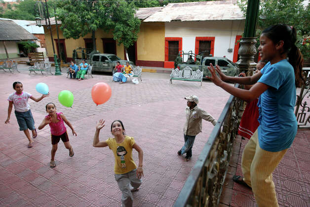 "With Mexican soldiers guarding the town of Batopilas, Mexico, children play in the square, Monday, Oct. 8, 2012. Located at the bottom of a canyon by the Batopilas River, the once-popular tourist destination remains largely untouched by modernity. With drug gangs fighting for the plaza, tourism has come to a standstill. ""It's a hugh crisis for Batopilas. Tourism supports a lot of people. It's very severe and the government can do very little,"" said city administrator Rafael Gastelum. Photo: Jerry Lara, San Antonio Express-News / San Antonio Express-News"