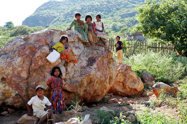 "Tarahumara childen hang out on a rock in the settlement of El Arenal de Los Lupes, near Batopilas, Mexico, Sunday, Oct. 7, 2012. The Tarahumara have historically lived through cyclical waves of hunger that was exacerbated by the drought last year. ""It was very bad here. You know the Tarahumara. They don't like to ask the government for anything, but this year they really needed help, so they ask for it,"" said Batopilas city adminstrator Rafael Ruelas Gastelum. Photo: Jerry Lara, San Antonio Express-News / San Antonio Express-News"