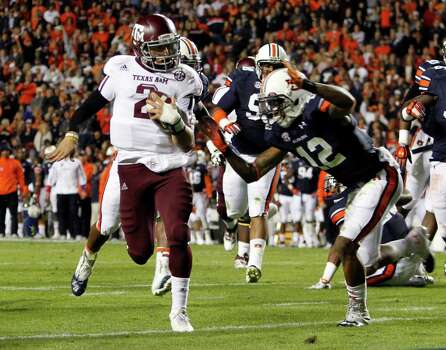 Texas A&M quarterback Johnny Manziel (2) runs in for a touchdown past Auburn defensive back Demetruce McNeal (12) during the first half of an NCAA college football game on Saturday, Oct. 27, 2012, in Auburn, Ala. (AP Photo/Butch Dill) Photo: Butch Dill, Associated Press / FR111446 AP