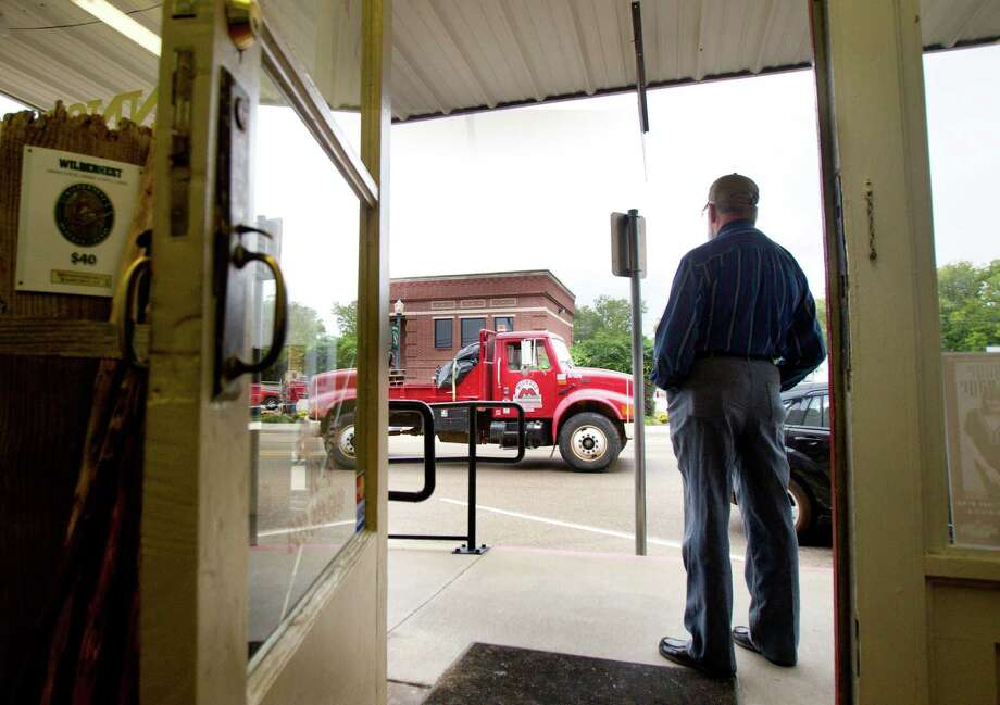 Conrad Wolfman watches from his storefront as a truck that hauls equipment for TransCanada's Keystone XL project drives through downtown Winnsboro, Thursday, Oct. 25, 2012, in Wood County. Photo: Cody Duty, Houston Chronicle / © 2012 Houston Chronicle
