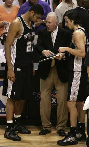 Spurs' coach Gregg Popovich (center) gives last minute instructions to players Tim Duncan (left) and Manu Ginobili during fourth quarter action game five Western Conference Finals at the America West Arena Wednesday June 1, 2005. KIN MAN HUI/Express-News (SAN ANTONIO EXPRESS-NEWS)