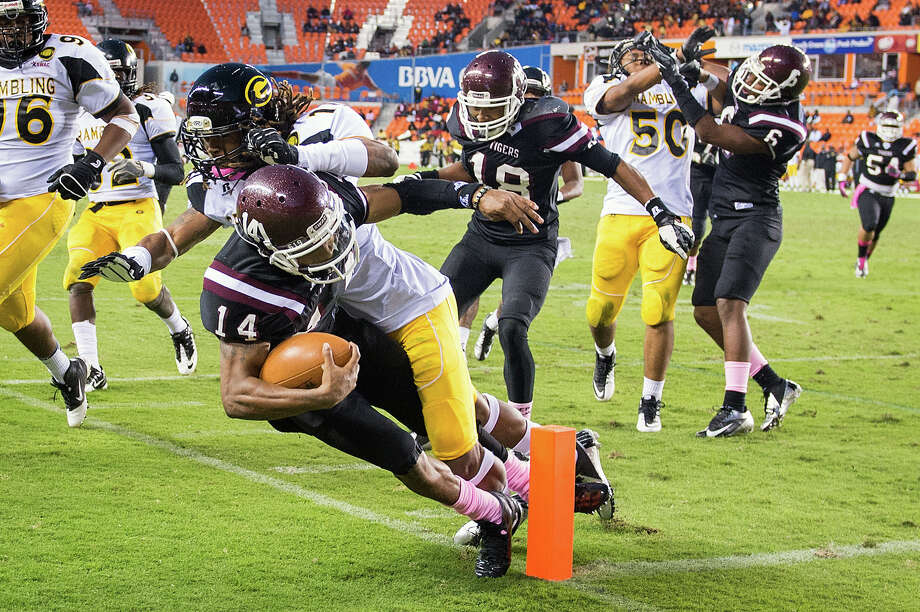 Texas Southern quarterback Rudy Johnson (14) is knocked out of bound just short of the goal line by Grambling defensive back De'Vontay Hogan (10) during the fourth quarter. Photo: Smiley N. Pool, Houston Chronicle / © 2012  Houston Chronicle