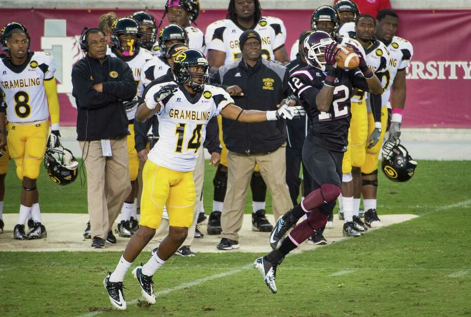 Texas Southern linebacker Eric Brown (12) steps in front of Grambling wide receiver Musa Mahmud (14) to intercept a pass during the fourth quarter .Brown returned the interception for a touchdown to tie the game. Photo: Smiley N. Pool, Houston Chronicle / © 2012  Houston Chronicle