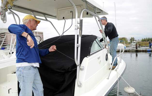 Glenn Pape, left, and Rob Carr, right, work to secure Pape's boat on Saturday, October 27, 2012, in preparation for the expected hurricane. Photo: Lindsay Niegelberg / CT