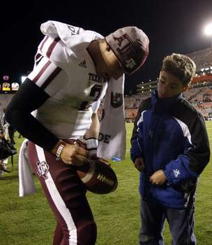 Texas A&M quarterback Johnny Manziel (2) signs a football after an NCAA college game where Texas A&M defeated Auburn 63-21 on Saturday, Oct. 27, 2012, in Auburn, Ala. (AP Photo/Butch Dill) (Associated Press)