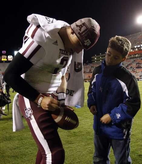 Texas A&M quarterback Johnny Manziel (2) signs a football after an NCAA college game where Texas A&M