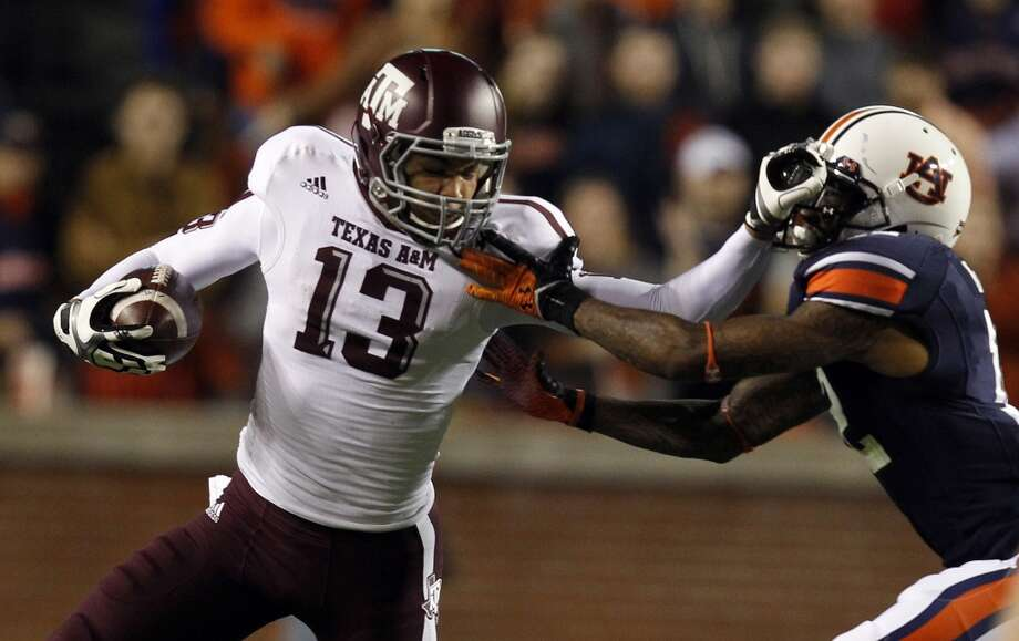 Texas A&M wide receiver Mike Evans (13) stiff-arms Auburn defensive back Demetruce McNeal (12) as he tries to reach the first-down marker during the first half of an NCAA college football game on Saturday, Oct. 27, 2012, in Auburn, Ala. (AP Photo/Butch Dill) (Associated Press)