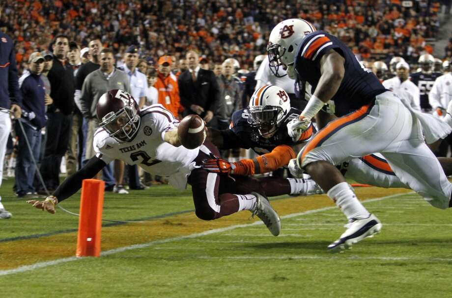 Texas A&M quarterback Johnny Manziel (2) dives for the end zone for a touchdown past Auburn linebacker Cassanova McKinzy (30) and Auburn linebacker Daren Bates (25) during the first half of an NCAA college football game on Saturday, Oct. 27, 2012, in Auburn, Ala. (AP Photo/Butch Dill) (Associated Press)