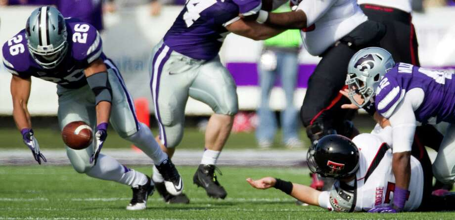 Kansas State's Jarell Childs scoops up a fumble by Tech's Seth Doege, right. Photo: SHANE KEYSER, MBR / ARCHIVE