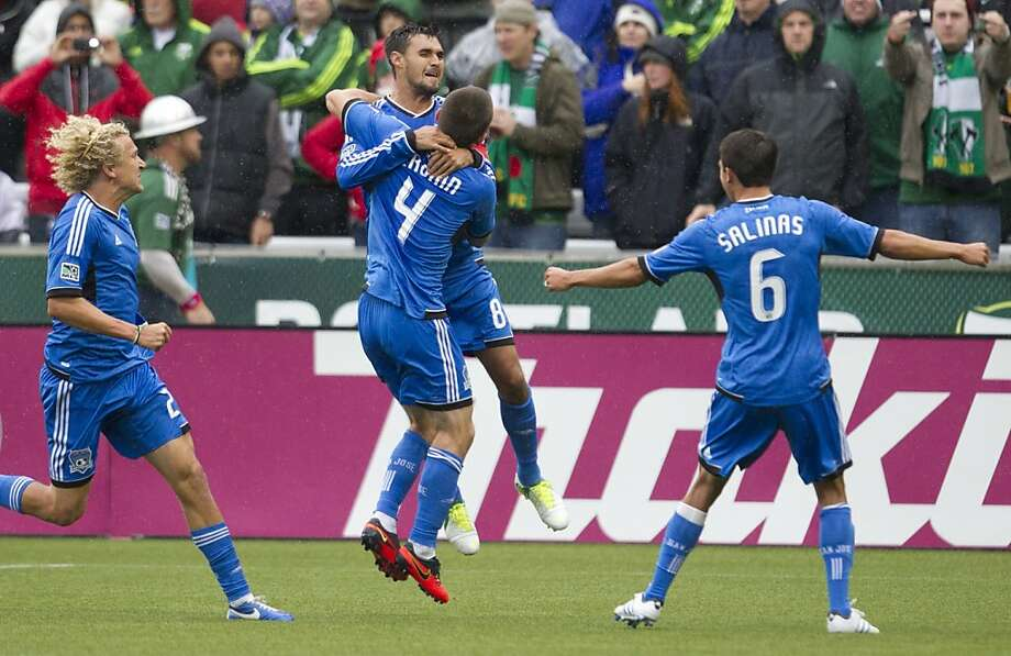 Teammates help Chris Wondolowski (center) celebrate the goal that tied the MLS record. Photo: Ross William Hamilton, Associated Press