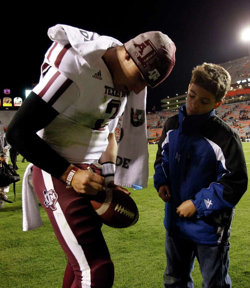 Texas A&M quarterback Johnny Manziel (2) signs a football after an NCAA college game where Texas A&M defeated Auburn 63-21 on Saturday, Oct. 27, 2012, in Auburn, Ala. (AP Photo/Butch Dill) Photo: Butch Dill, Associated Press / FR111446 AP