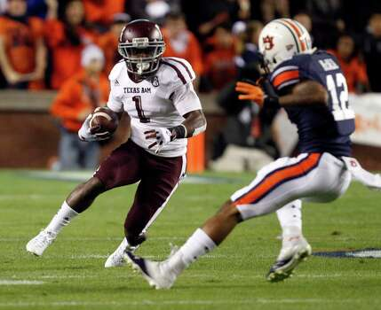 Texas A&M running back Ben Malena (1) tries to get around Auburn defensive back Demetruce McNeal (12) during the first half of an NCAA college football game on Saturday, Oct. 27, 2012, in Auburn, Ala. Texas A&M defeated Auburn 63-21. (AP Photo/Butch Dill) Photo: Butch Dill, Associated Press / FR111446 AP