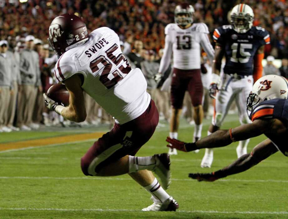 Texas A&M wide receiver Ryan Swope (25) catches a pass for a touchdown past Auburn defensive end Craig Sanders (13) during the first half of an NCAA college football game on Saturday, Oct. 27, 2012, in Auburn, Ala. (AP Photo/Butch Dill) Photo: Butch Dill, Associated Press / FR111446 AP