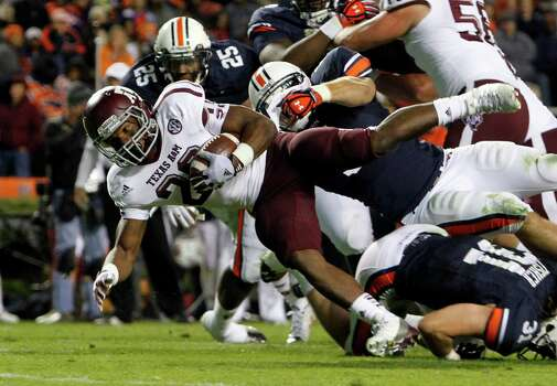 Texas A&M running back Trey Williams (20) stretches for the end zone but comes up short as he is tackled by Auburn linebacker Jake Holland (5) during the second half of an NCAA college football game on Saturday, Oct. 27, 2012, in Auburn, Ala. (AP Photo/Butch Dill) Photo: Butch Dill, Associated Press / FR111446 AP