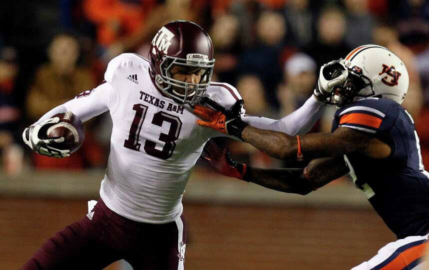 Texas A&M wide receiver Mike Evans (13) stiff-arms Auburn defensive back Demetruce McNeal (12) as he